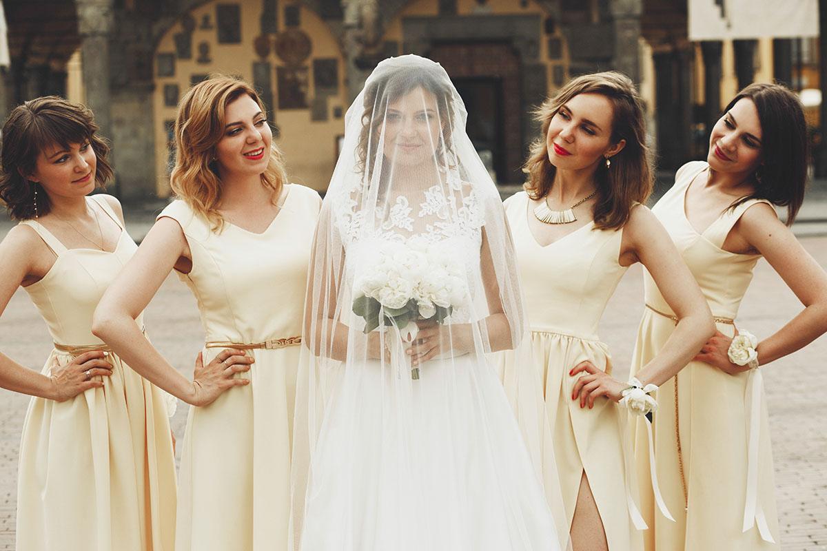 Pretty bridesmaids in yellow dresses stand behind bride hidden u